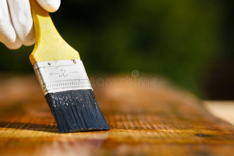 Πινέλο που γλιστρά πέρα από την ξύλινη επιφάνεια, που προστατεύει το ξύλο στοκ φωτογραφία
