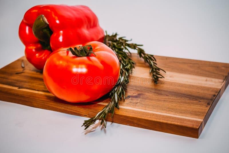Πιπέρια κουδουνιών, δεντρολίβανο, ντομάτες, συστατικά για το μαγείρεμα στο ξύλινο αγροτικό υπόβαθρο, θέση για το κείμενο ακατέργα στοκ εικόνες