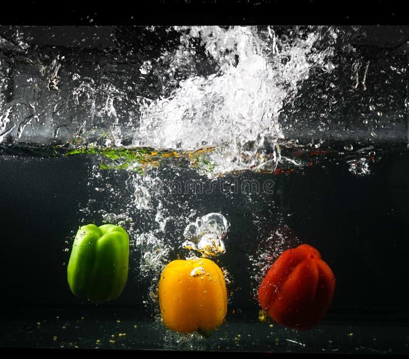 πιπέρια κουδουνιών Μια ομάδα γλυκών πιπεριών που πέφτουν κάτω και splashin στοκ φωτογραφίες