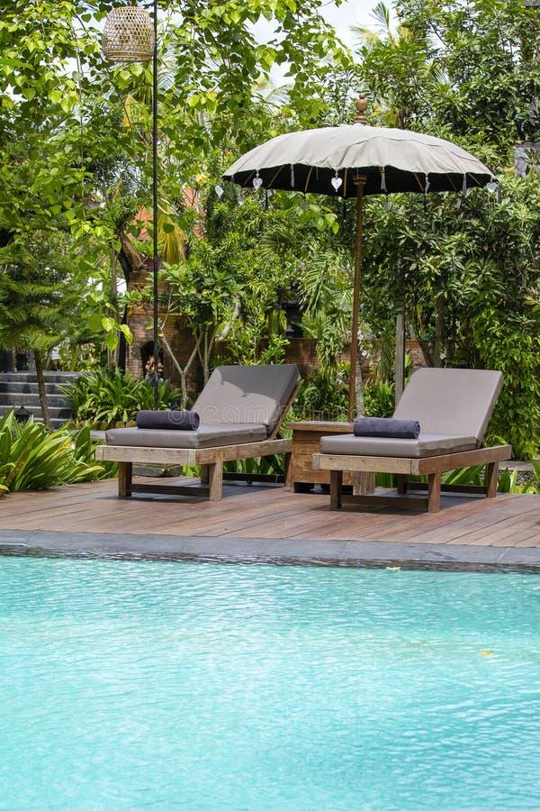 Πισίνα, μπλε νερό, πράσινα φύλλα των δέντρων και καρέκλες γεφυρών στον τροπικό κήπο Νησί Μπαλί, Ινδονησία στοκ εικόνα
