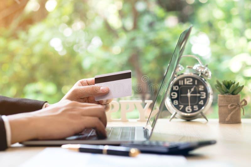 Πιστωτική κάρτα εκμετάλλευσης χεριών επιχειρηματιών και χρησιμοποίηση του lap-top στα WI γραφείων στοκ φωτογραφίες με δικαίωμα ελεύθερης χρήσης