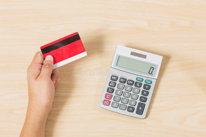 Πιστωτική κάρτα εκμετάλλευσης χεριών και τεθειμένος υπολογιστής στο ξύλο στοκ εικόνα