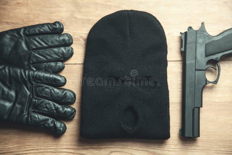 Πιστόλι, balaclava και γάντια στο ξύλινο υπόβαθρο Εγκληματικός συμπυκνωμένος στοκ εικόνα με δικαίωμα ελεύθερης χρήσης