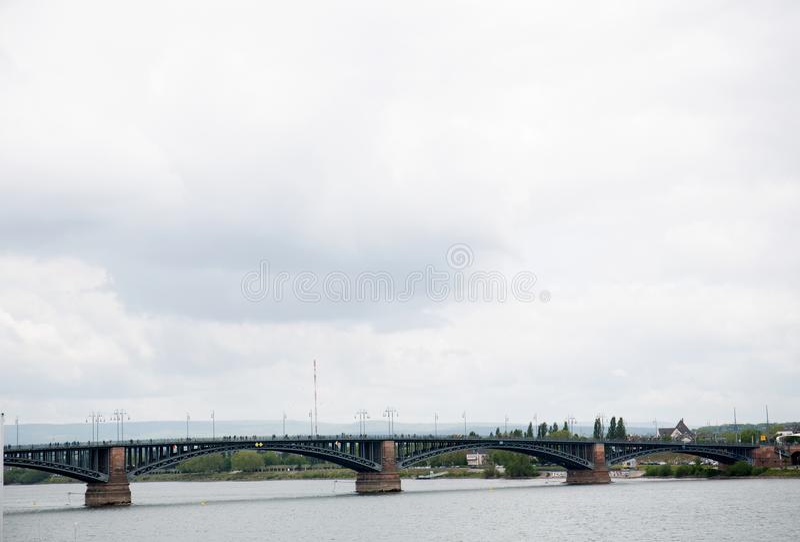 Πιό στενή άποψη σχετικά με μια γέφυρα και τα κτήρια κάτω από έναν νεφελώδη ουρανό στο Μάιντς Γερμανία στοκ φωτογραφίες