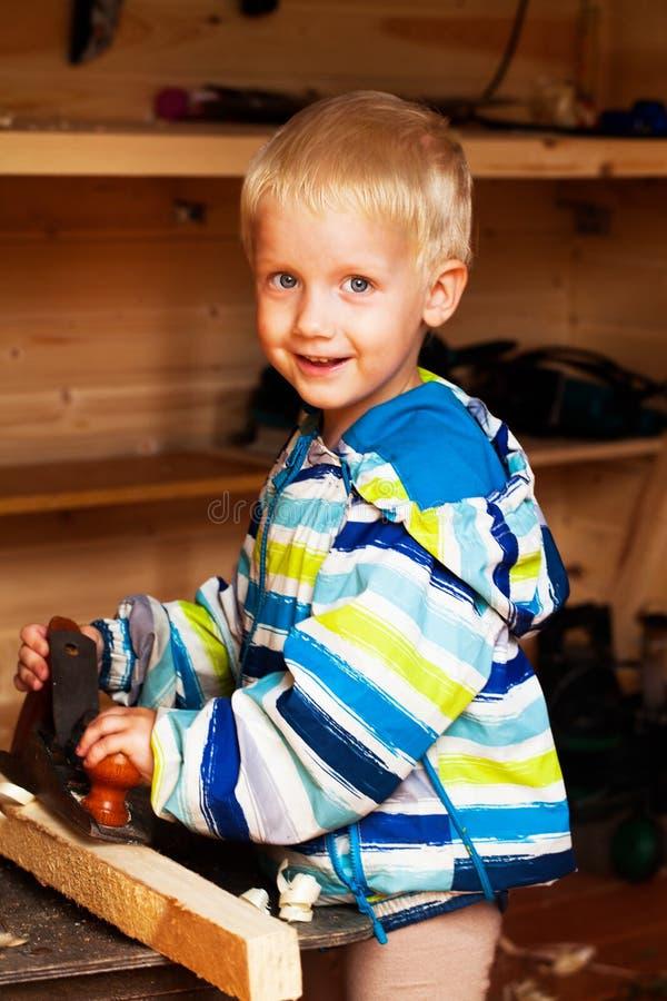 Πιό χαριτωμένο αγόρι στο εργαστήριο ενός ξυλουργού που προγραμματίζεται στοκ φωτογραφία με δικαίωμα ελεύθερης χρήσης