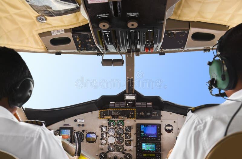 Πιλότοι στο πιλοτήριο και τον ουρανό αεροπλάνων στοκ φωτογραφία