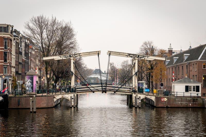 Πλάγια όψη διάσημο ξύλινο drawbridge που βλέπει από το νερό με τα κτήρια στο υπόβαθρο στο Άμστερνταμ στοκ φωτογραφία με δικαίωμα ελεύθερης χρήσης