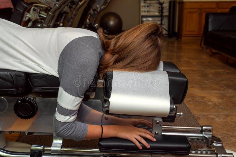 Πλάγια όψη ενός κοριτσιού που βάζει σε έναν γαρμένο Chiropractic πίνακα στοκ φωτογραφία
