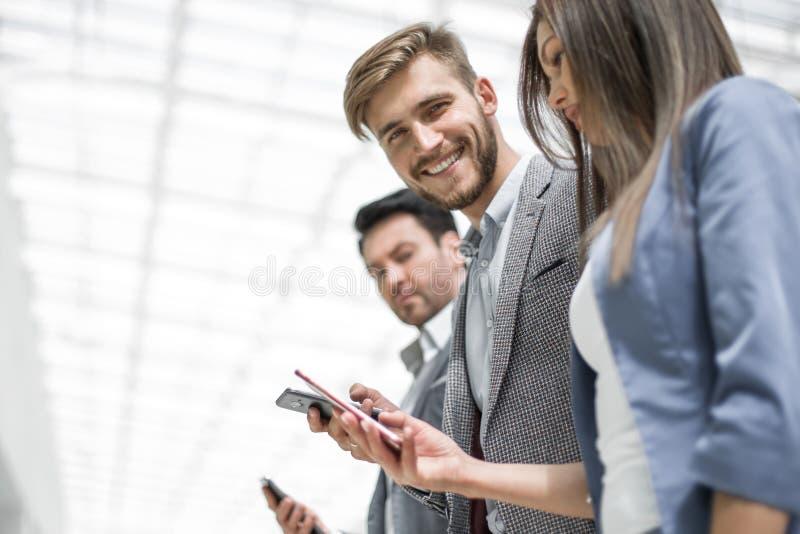 Πλάγια όψη επιχειρησιακή ομάδα που εξετάζει τις οθόνες του smartpho τους στοκ φωτογραφία