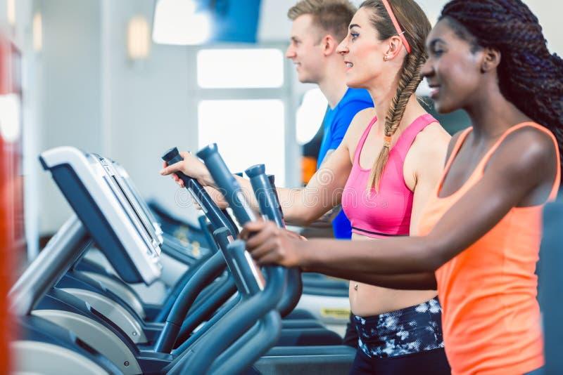 Πλάγια όψη μιας κατάλληλης ευτυχούς γυναίκας και της εκπαιδευτικής ομάδας της σχετικά με treadmill στοκ εικόνες
