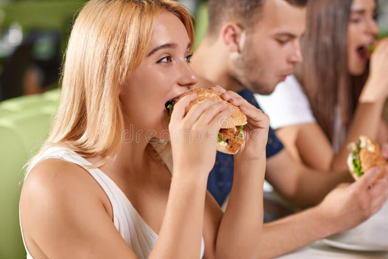 Πλάγια όψη πεινασμένο ξανθό μεγάλο juicy burger δαγκώματος στοκ φωτογραφία