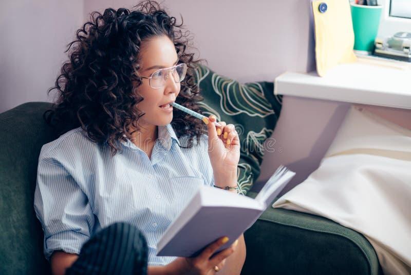 Πλάγια όψη που πυροβολείται της γυναίκας που έχει το μολύβι στο στόμα και που κρατά το βιβλίο στο εσωτερικό στοκ εικόνες