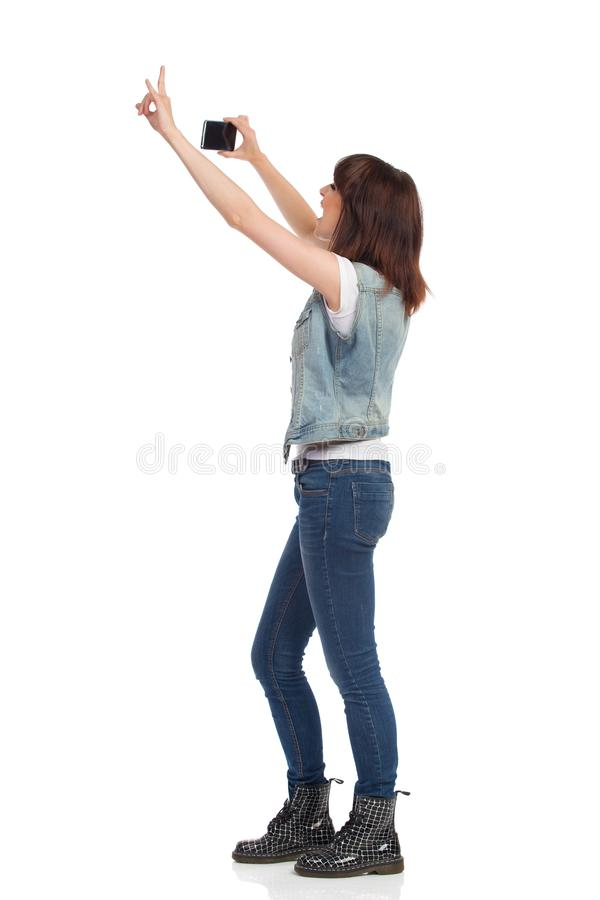 Πλάγια όψη της γυναίκας που παίρνει τη φωτογραφία με ένα τηλέφωνο κυττάρων στοκ εικόνες