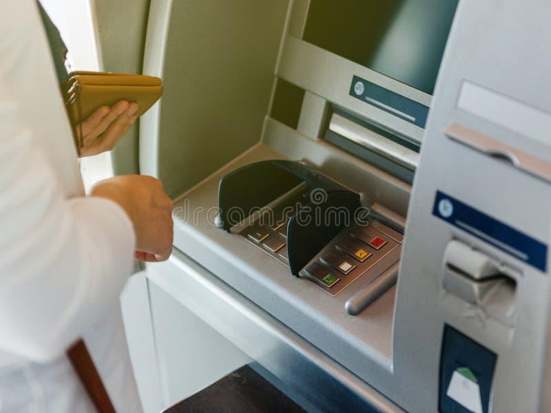 Πλάγια όψη της γυναίκας που χρησιμοποιεί το πορτοφόλι εκμετάλλευσης του ATM μια συμπίεση η ΚΑΡΦΊΤΣΑ στοκ εικόνα