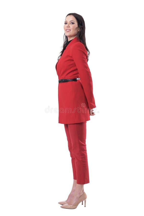 Πλάγια όψη της ευτυχούς βέβαιας νέας επιχειρησιακής γυναίκας στο κόκκινο κοστούμι που γυρίζει και που εξετάζει τη κάμερα στοκ φωτογραφία