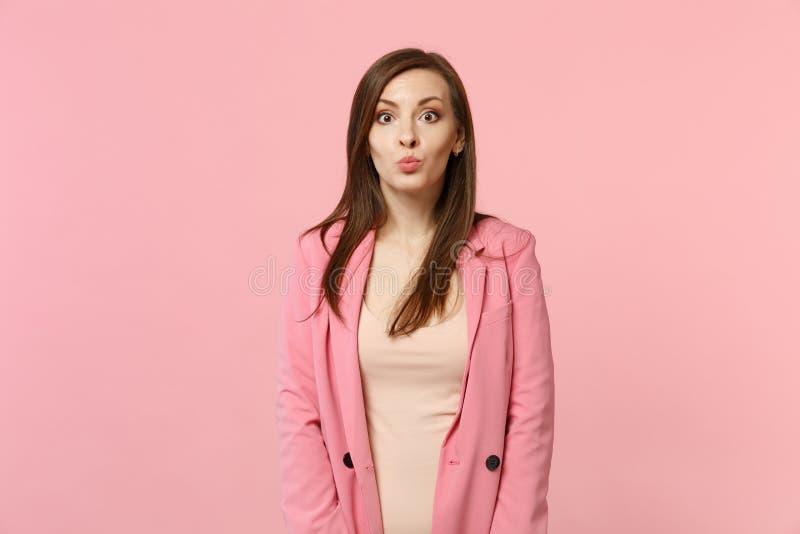 Πλάγια όψη της εύθυμης αστείας αρκετά νέας γυναίκας στο σακάκι που φαίνεται κάμερα, φυσώντας χείλια που απομονώνονται στο ρόδινο  στοκ φωτογραφίες με δικαίωμα ελεύθερης χρήσης