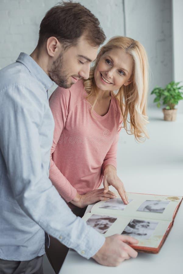 πλάγια όψη της μητέρας και του αυξημένου γιου που εξετάζουν το λεύκωμα φωτογραφιών από κοινού στοκ εικόνες