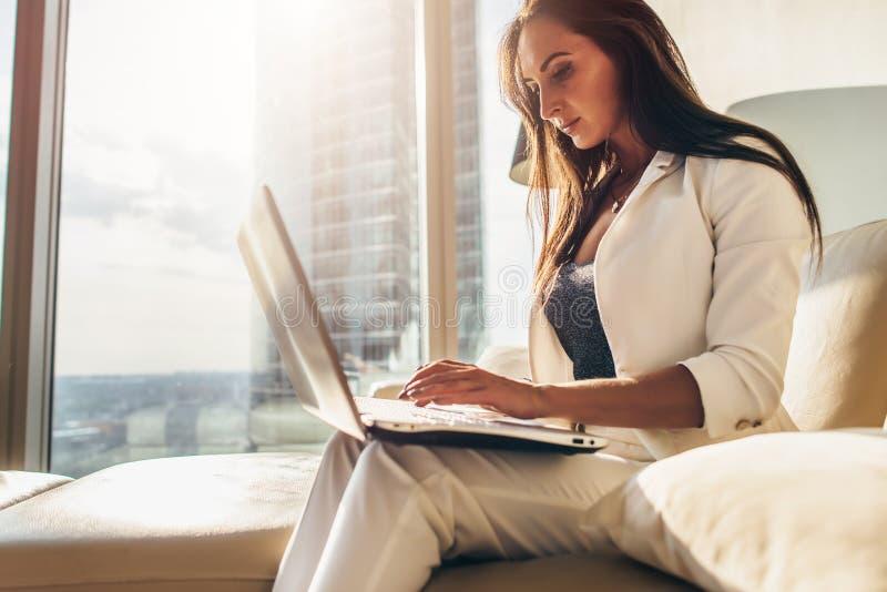 Πλάγια όψη της νέας γυναίκας που εργάζεται στο lap-top στοκ φωτογραφία με δικαίωμα ελεύθερης χρήσης