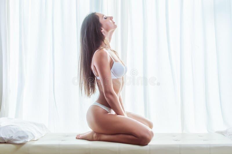 Πλάγια όψη της νέας γυναίκας brunette που φορά lingerie τη συνεδρίαση στο άσπρο κρεβάτι με το παράθυρο και τις κουρτίνες στο υπόβ στοκ εικόνες