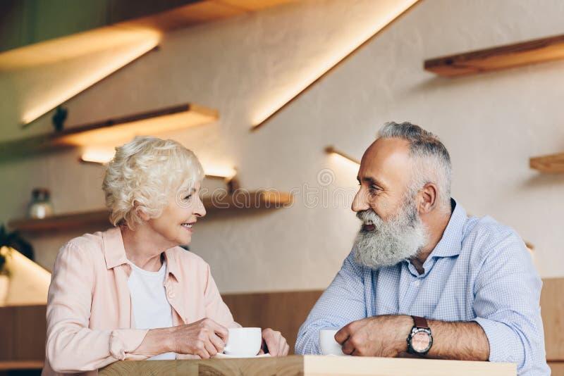 πλάγια όψη του ανώτερου ζεύγους που έχει τη συνομιλία πίνοντας τον καφέ από κοινού στοκ φωτογραφία με δικαίωμα ελεύθερης χρήσης