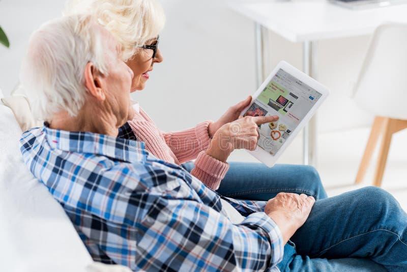 πλάγια όψη του ανώτερου ζεύγους που χρησιμοποιεί την ψηφιακή ταμπλέτα με ebay στοκ φωτογραφία