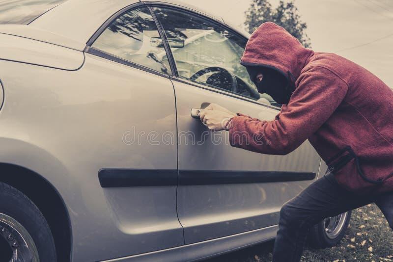 Πλάγια όψη του αυτοκινήτου που αναγκάζεται από ένα άτομο στο hoodie και τη μάσκα Ο κλέφτης προσπαθεί να κλέψει το όχημα από έναν  στοκ φωτογραφίες με δικαίωμα ελεύθερης χρήσης