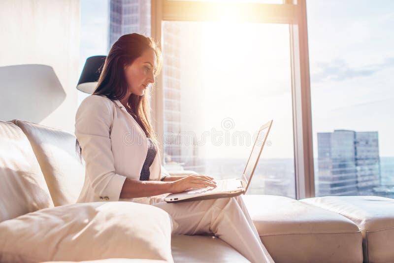 Πλάγια όψη του επιτυχούς νέου θηλυκού που εργάζεται στο lap-top στοκ εικόνα