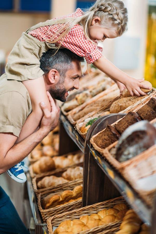 πλάγια όψη του ευτυχούς ψωμιού αγοράς πατέρων και κορών στοκ εικόνα με δικαίωμα ελεύθερης χρήσης