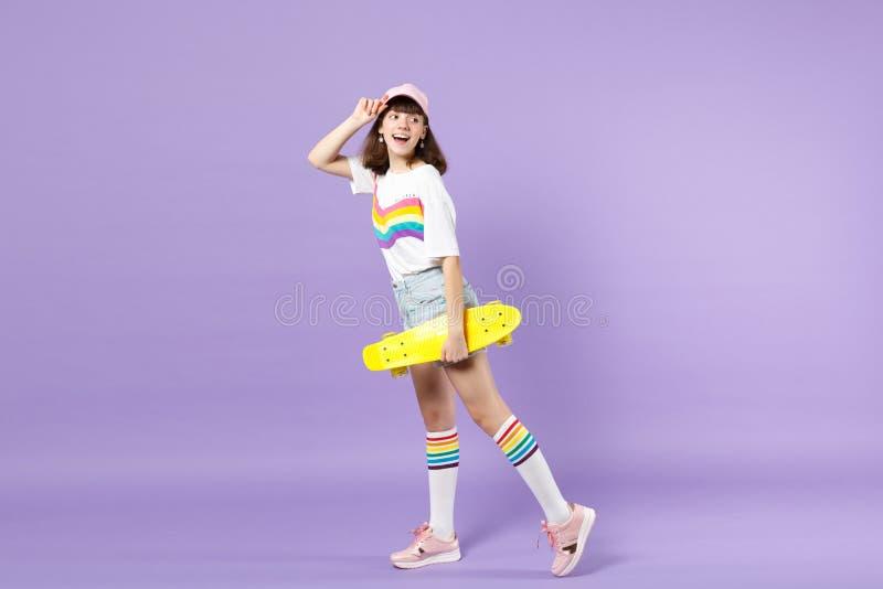 Πλάγια όψη του εύθυμου κοριτσιού εφήβων στα ζωηρά ενδύματα που κρατά κίτρινο skateboard, που φαίνεται πίσω απομονωμένη στην ιώδη  στοκ φωτογραφία με δικαίωμα ελεύθερης χρήσης