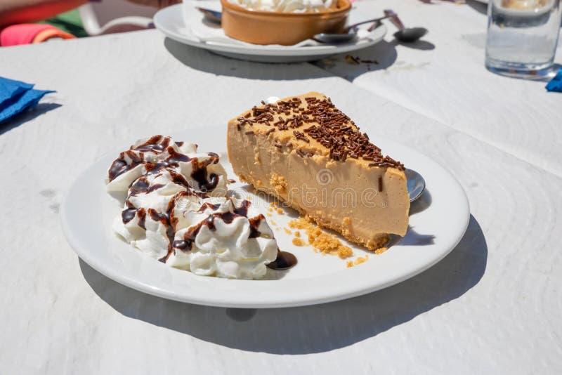 Πλάγια όψη του κομματιού του κέικ και της κρέμας σοκολάτας στο άσπρο πιάτο στοκ εικόνες