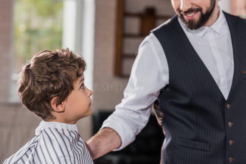 πλάγια όψη του λατρευτού παιδάκι που καλύπτεται με τη ριγωτή συνεδρίαση υφασμάτων στοκ φωτογραφία με δικαίωμα ελεύθερης χρήσης
