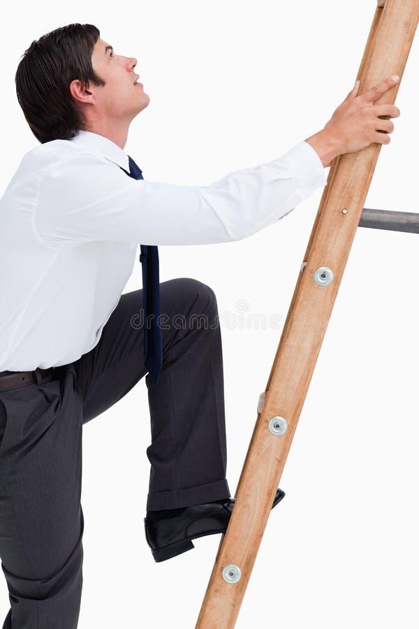 Πλάγια όψη του νέου καταστηματάρχη που αναρριχείται σε μια σκάλα στοκ εικόνες