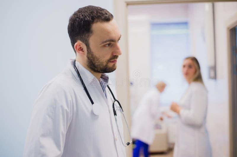 Πλάγια όψη του στοχαστικού νέου γιατρού στο ιατρικό ομοιόμορφο άκουσμα τον ασθενή στοκ φωτογραφία