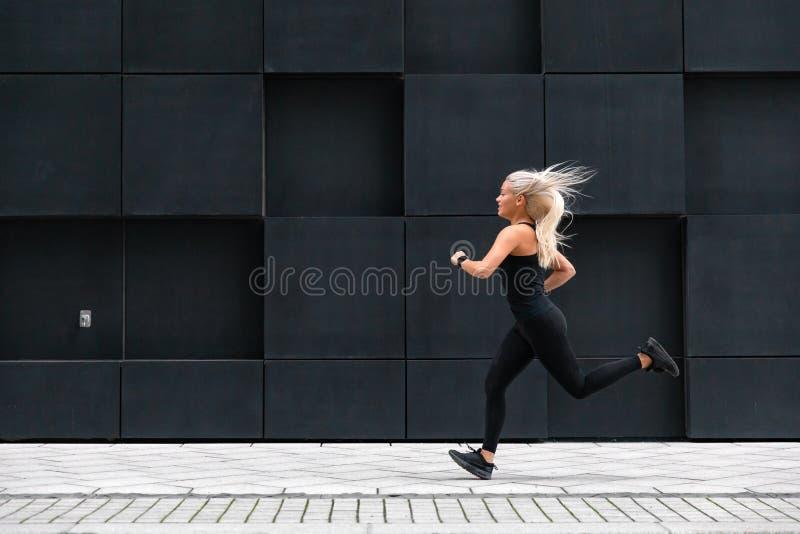 Πλάγια όψη του φίλαθλου νέου τρεξίματος γυναικών γρήγορα στο μινιμαλιστικό αστικό περιβάλλον στοκ εικόνες