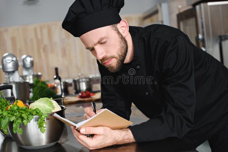 πλάγια όψη του όμορφου αρχιμάγειρα που γράφει κάτω τη νέα συνταγή στο σημειωματάριο στοκ εικόνες