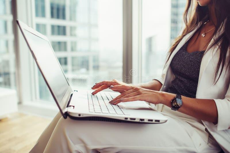 Πλάγια όψη του lap-top εκμετάλλευσης γυναικών στην εργασία περιτυλίξεών της στην αρχή στοκ φωτογραφία