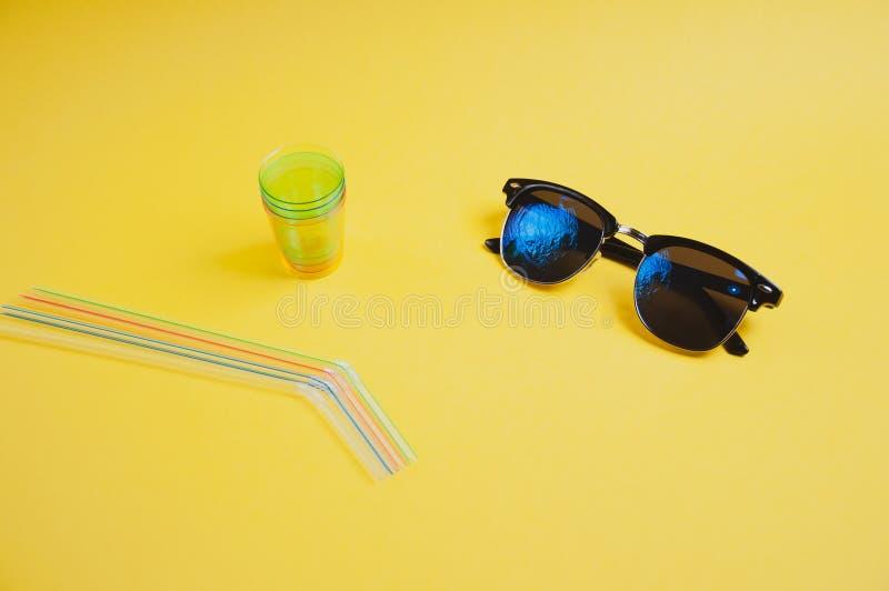 Πλάγια όψη των ζωηρόχρωμων αχύρων, του γυαλιού και των γυαλιών ηλίου στο κίτρινο υπόβαθρο, με το διάστημα αντιγράφων στοκ εικόνες