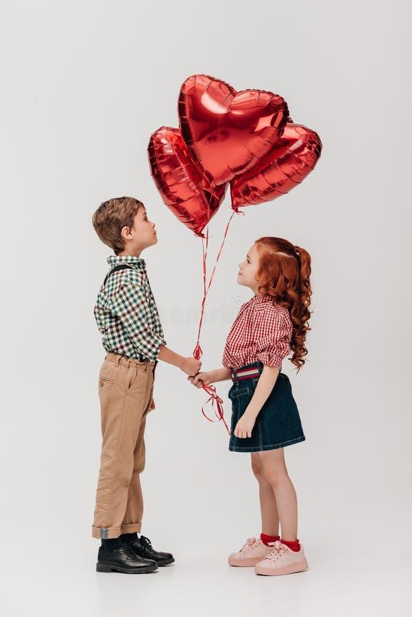 πλάγια όψη των όμορφων λίγη διαμορφωμένων καρδιά μπαλονιών εκμετάλλευσης ζευγών στοκ φωτογραφία