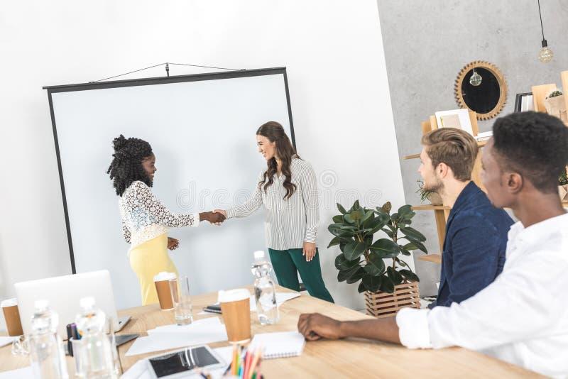 πλάγια όψη των multiethnic νέων επιχειρηματιών που τινάζουν τα χέρια κατά τη διάρκεια στοκ φωτογραφία με δικαίωμα ελεύθερης χρήσης