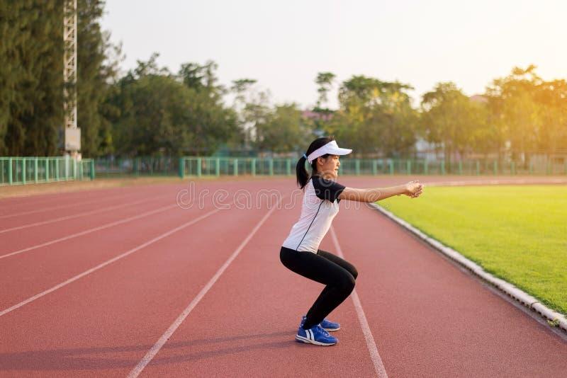 Πλάγια όψη φίλαθλο να κάνει γυναικών αθλητισμού ασιατικό της καθμένος οκλαδόν, όμορφης θηλυκής λεπτής γυναικείας πρότυπης πρακτικ στοκ εικόνες