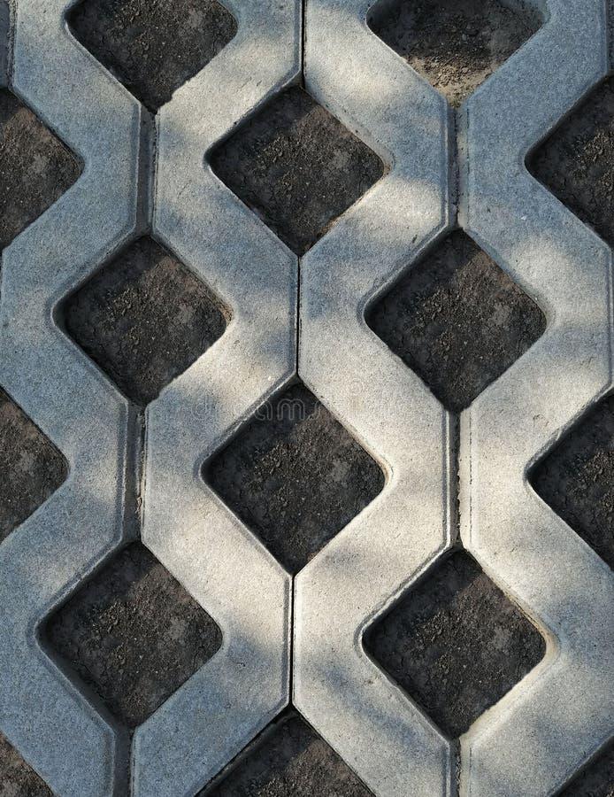 Πλάκες επίστρωσης του γκρίζου χρώματος στη γη υπό μορφή πλέγματος για τη χλόη στοκ φωτογραφία