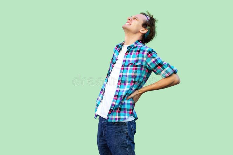 Πλάτη ή πόνος σπονδυλικών στηλών Πορτρέτο πλάγιας όψης σχεδιαγράμματος του κουρασμένου νεαρού άνδρα στο περιστασιακό μπλε ελεγμέν στοκ εικόνα με δικαίωμα ελεύθερης χρήσης