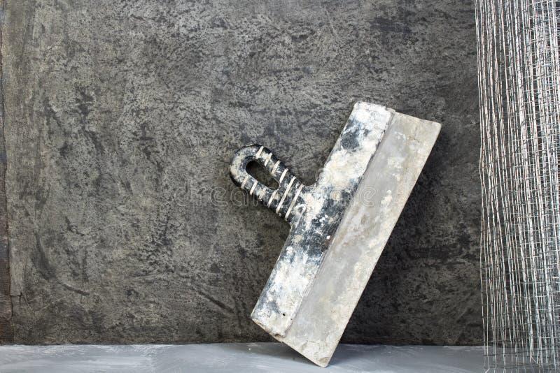 Πλέγμα ρόλων για την επικονίαση, putty μαχαίρι στο γκρίζο συγκεκριμένο υπόβαθρο r r στοκ φωτογραφίες