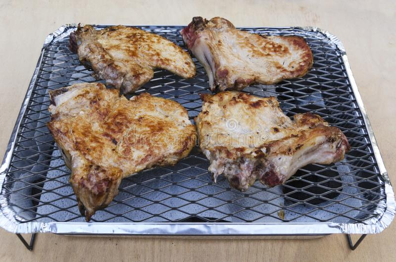 Πλέγμα σχαρών και κομμάτια των ψημένων μπριζολών χοιρινού κρέατος σε το στοκ φωτογραφία με δικαίωμα ελεύθερης χρήσης