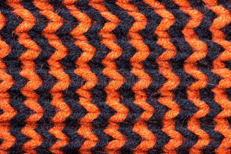Πλέξιμο Πλεκτή υπόβαθρο σύσταση Φωτεινές πλέκοντας βελόνες Πορτοκαλί και μαύρο νήμα μαλλιού για το πλέξιμο στοκ φωτογραφία