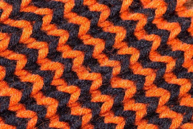 Πλέξιμο Πλεκτή υπόβαθρο σύσταση Φωτεινές πλέκοντας βελόνες Πορτοκαλί και μαύρο νήμα μαλλιού για το πλέξιμο στοκ εικόνες