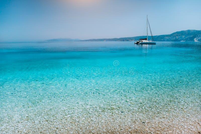 Πλέοντας βάρκα γιοτ καταμαράν στην άγκυρα κοντά στην παραλία χαλικιών με την ήρεμη καθαρή σαφή κυανή μπλε επιφάνεια νερού στοκ φωτογραφία