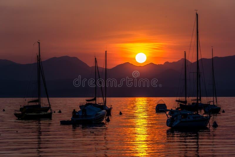 Πλέοντας βάρκες στη λίμνη Garda με το ηλιοβασίλεμα, Ιταλία στοκ εικόνες με δικαίωμα ελεύθερης χρήσης