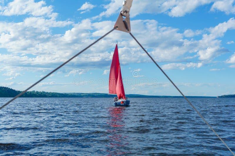 Πλέοντας μικρό γιοτ με τα κόκκινα πανιά, ορατά από μια άλλη βάρκα μέσω της λεπτομέρειας ξαρτιών στοκ εικόνα
