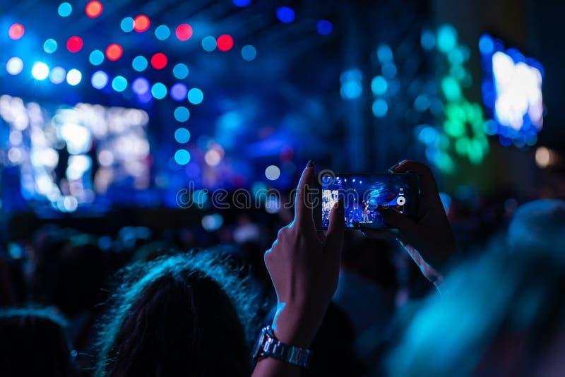 Πλήθη που καταγράφουν μια συναυλία στα κινητά τηλέφωνα στοκ εικόνες